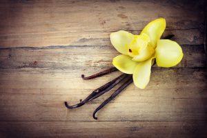 Vanilla Pods and Flower over Wooden Background. Vanilla Pod Stic