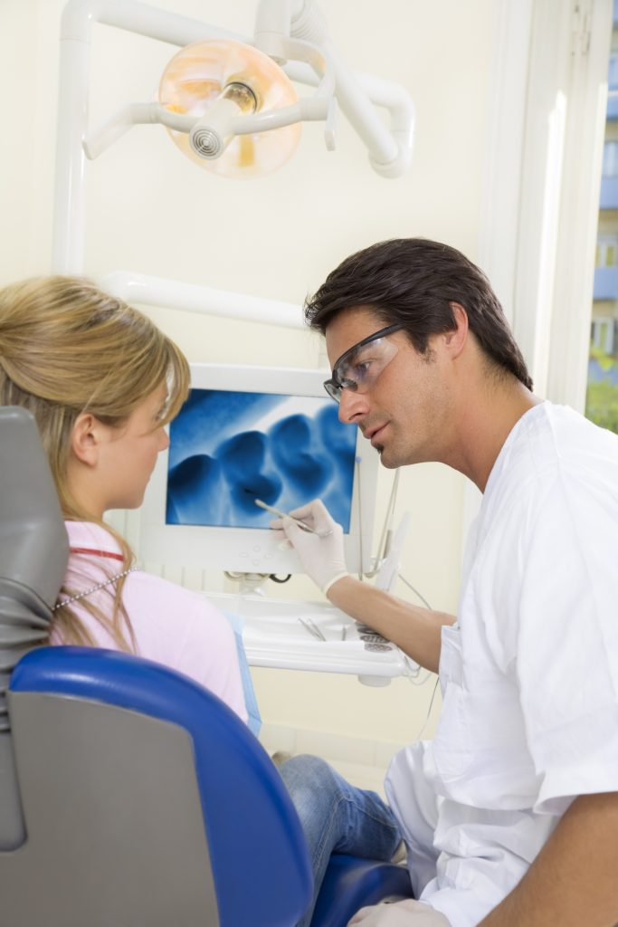 dentist talking to his patient and showing her a x-ray image of her teeth