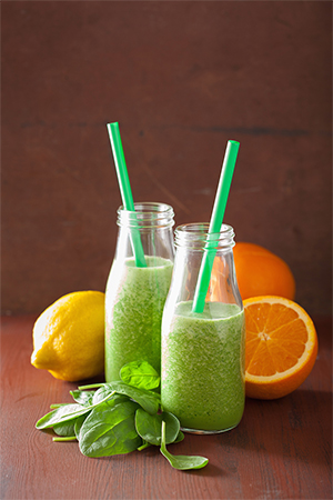 healthy green spinach smoothie with lemon orange